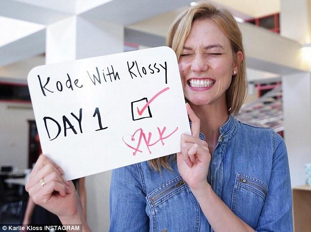 Karlie Kloss veste camisa jeans e sorri com plaquinha escrito Kode with Klossy Day 1.